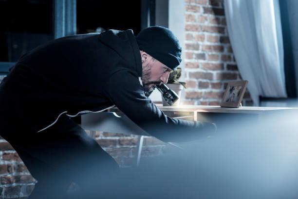 Ladrão profissional à procura de documentos na tabela - foto de acervo