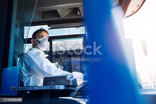 Driving bus public transportation during global pandemic of COVID-19. Professional bus driver in white protective suit wearing mask and gloves as prevention against highly contagious coronavirus.