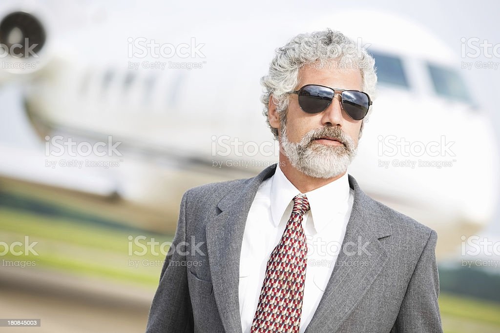 Professional business executive wearing aviator sunglasses at private jet airport royalty-free stock photo
