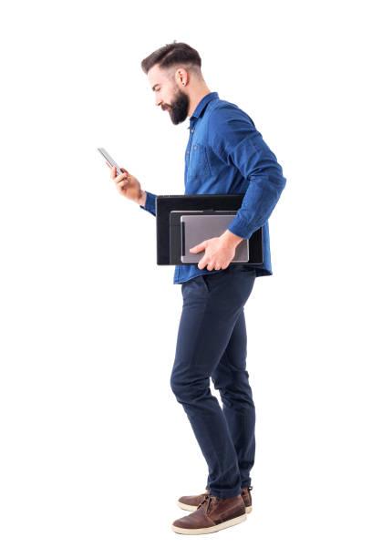 professionelle männliche führungskraft überprüft telefon, tablet und laptop unter dem arm tragen. seitenansicht. - mann freisteller stock-fotos und bilder