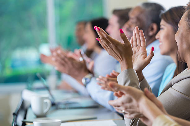 Professional business people applauding speaker at seminar or conference stock photo