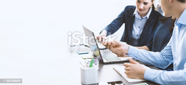 Professional business team working together, they are sitting at desk and using a laptop, teamwork and technology concept