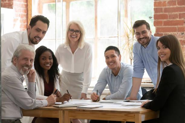 équipe professionnelle d'affaires jeunes et vieux posant à la table - groupe heureux photos et images de collection
