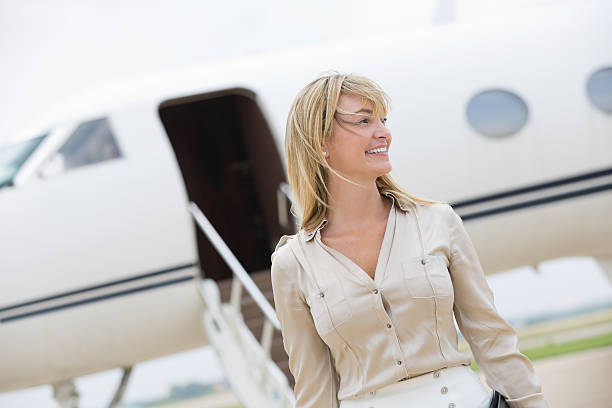 Professional businesswoman exiting private jet stock photo