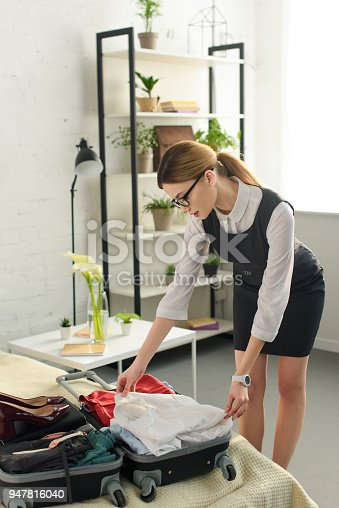 istock professional businesswoman packing suitcase for business trip 947816040