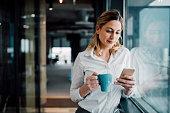 Beautiful business woman Texting in the coffee break