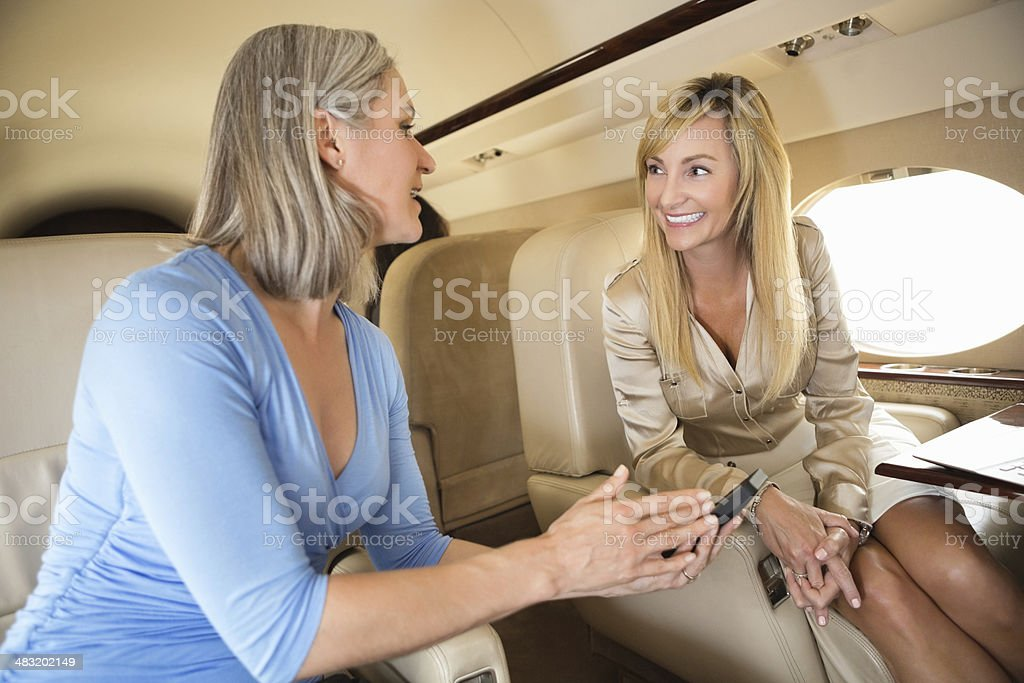 Professional businesswomen discussing business during private jet flight stock photo