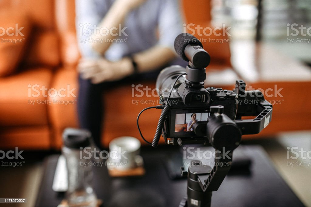 Professional camera filming a video podcast Influencer  recording a video with professional camera, focus on foreground Adult Stock Photo