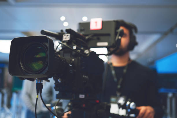 Professional cameraman with headphones with HD camcorder in live television Home Video Camera, Studio - Workplace, Filming, Television Set, Camera Operator ultra high definition television stock pictures, royalty-free photos & images