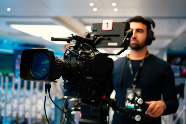 Professional cameraman with headphones with HD camcorder in live television stock photo