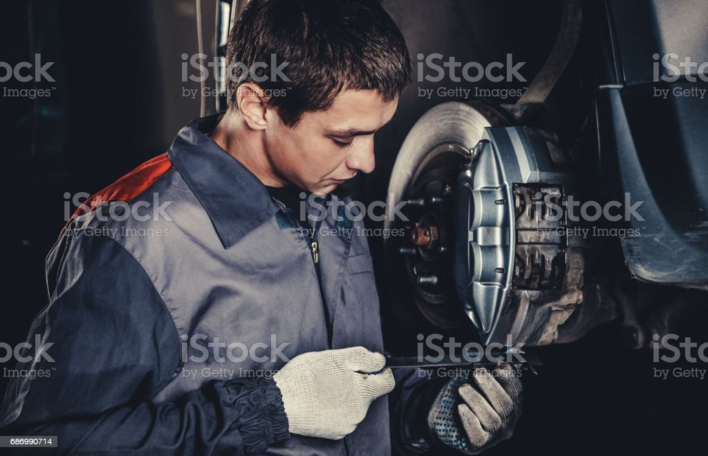 Professional car mechanic repairing brakes stock photo