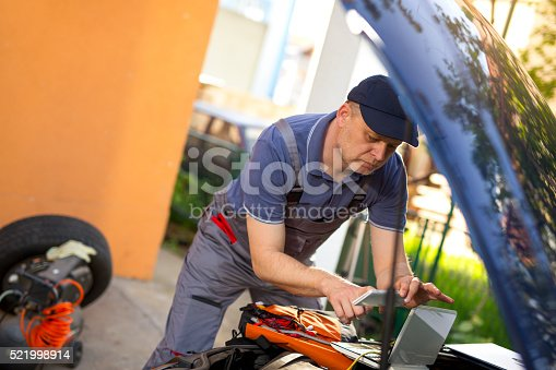 istock Professional car mechanic using smartphone to take picture 521998914