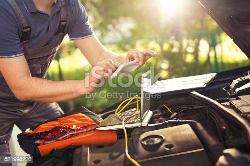istock Professional car mechanic using smartphoneto take pictures 521998722