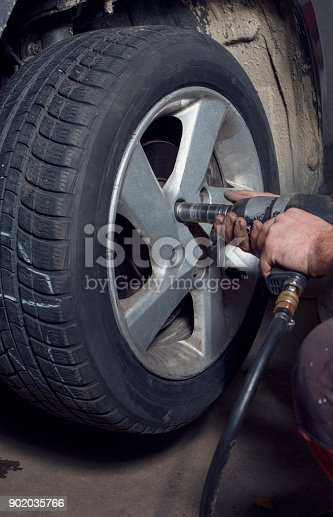 498888104 istock photo Professional car mechanic working with pneumatic wrench in auto service 902035766