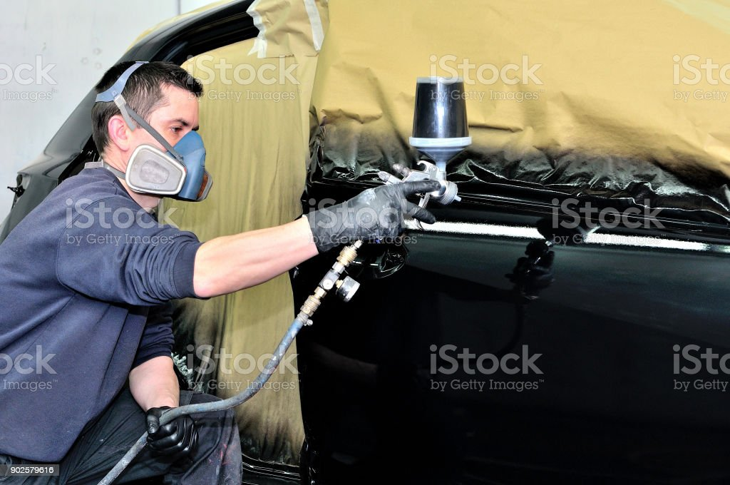 Professional car painter working at a black vehicle. stock photo