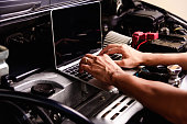 istock Professional car repair or maintenance mechanic engine working service with laptop computer 1189648037