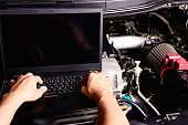 istock Professional car repair or maintenance mechanic engine working service with laptop 1204946618