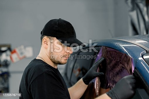 Professional car service worker wearing black cap and t-shirt, tinting a car window with tinted foil or film in auto workshop. Tinting of car windows.