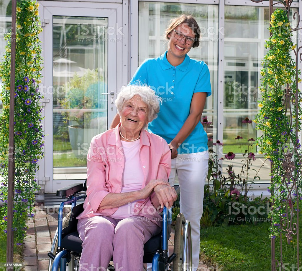 Professional carer behind happy elderly woman. stock photo