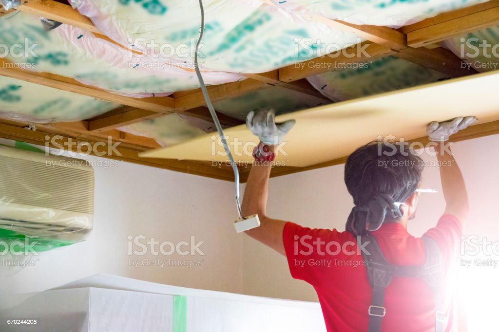 Professional carpenter is fixing the ceiling stock photo