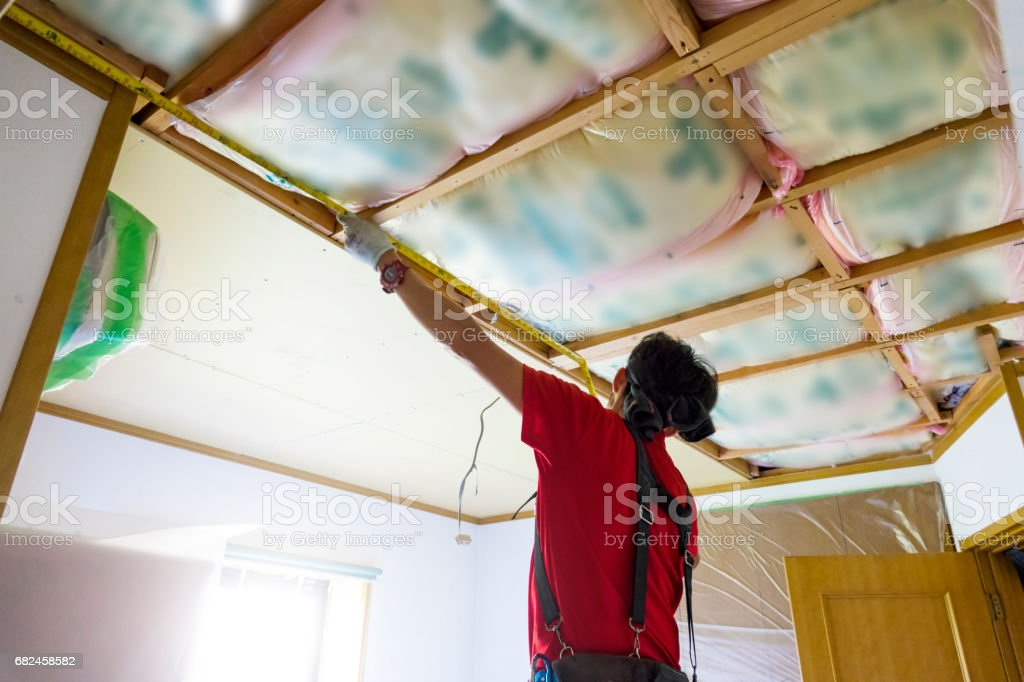 Professional carpenter is fixing the ceiling royalty-free stock photo