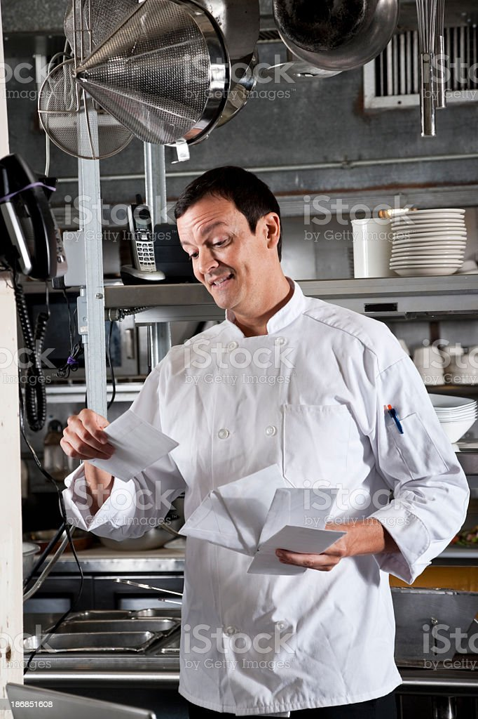 Professional chef and restaurant owner looking through mail stock photo