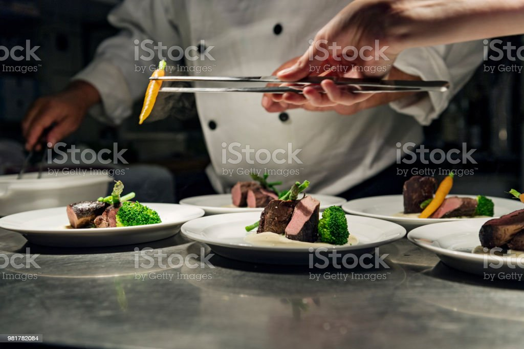 Professional Chef at work in a busy kitchen getting ready for service - Стоковые фото 55-59 лет роялти-фри