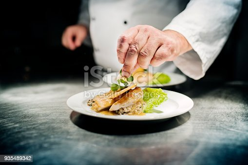 Professional chef putting the final flourish to the dish by adding a sprig of watercress to the dish of slow cooked chicken breast served on a bed of bulgur risotto. Colour, horizontal with some copy space. Photographed in a restaurant on the island of Møn in Denmark.