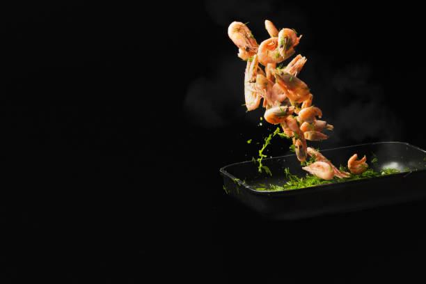 chef professionnel cuit des crevettes. cuisine fruits de mer et de l'alimentation sur un fond sombre. photo de l'hôtel. vue horizontale. - cuisine asiatique photos et images de collection