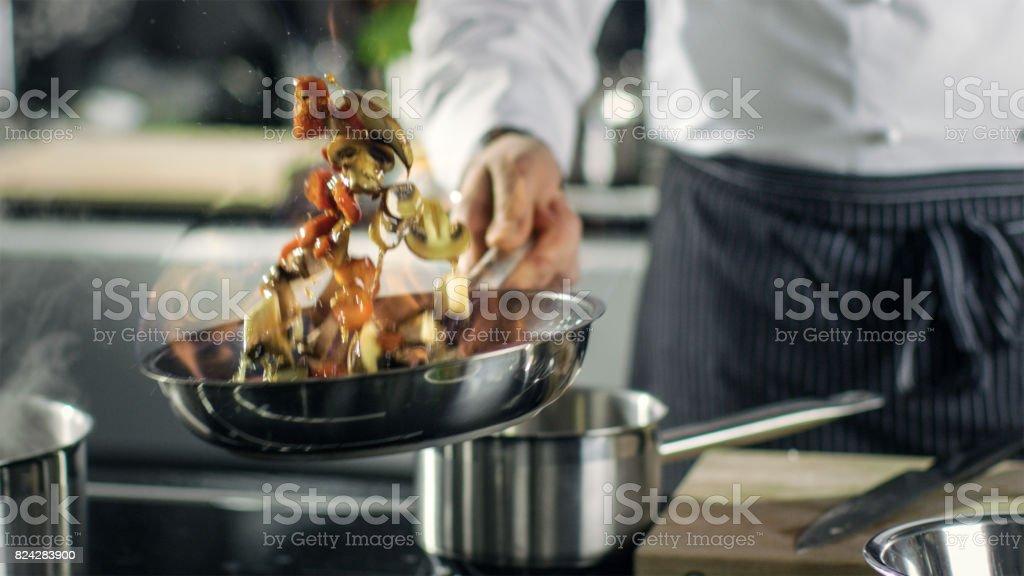Chef professionnel cuisiniers Flambe Style. Il prépare le plat dans une poêle avec une flamme nue. Il travaille dans une cuisine moderne avec différents ingrédients qui traînent. - Photo