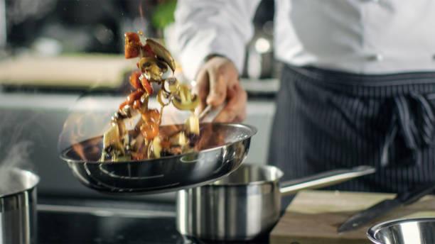 professionele chef koks geflambeerd stijl. hij bereidt de schotel in een pan met open vlammen. hij werkt in een moderne keuken met verschillende ingrediënten rondslingeren. - oil kitchen stockfoto's en -beelden