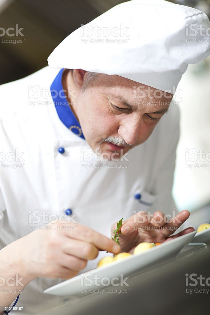 Professional chef garnishing a dish stock photo