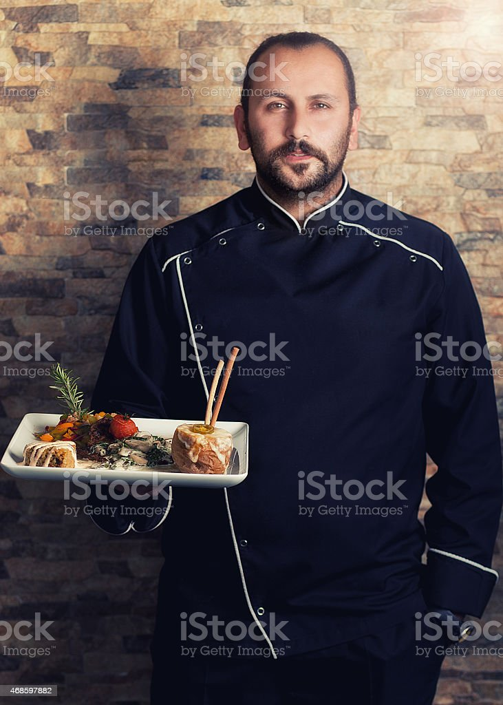 professional chef, holding a dinner plate stock photo
