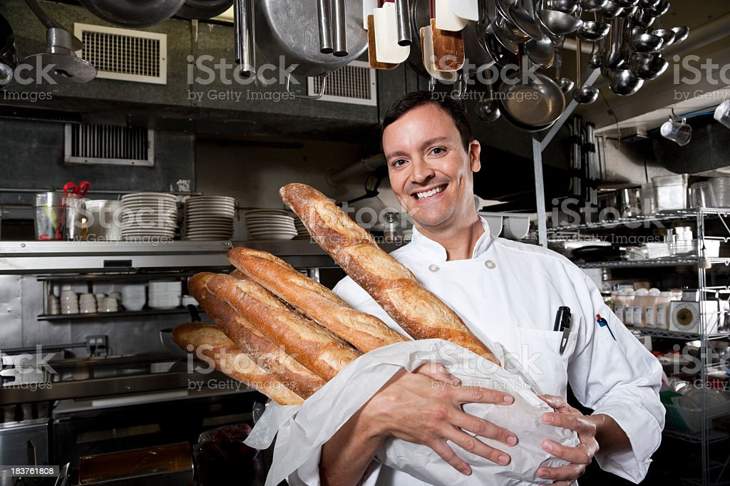 Professional chef holding loaves of freshly baked bread stock photo