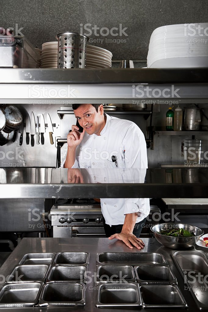 Professional chef in commercial kitchen on mobile phone stock photo
