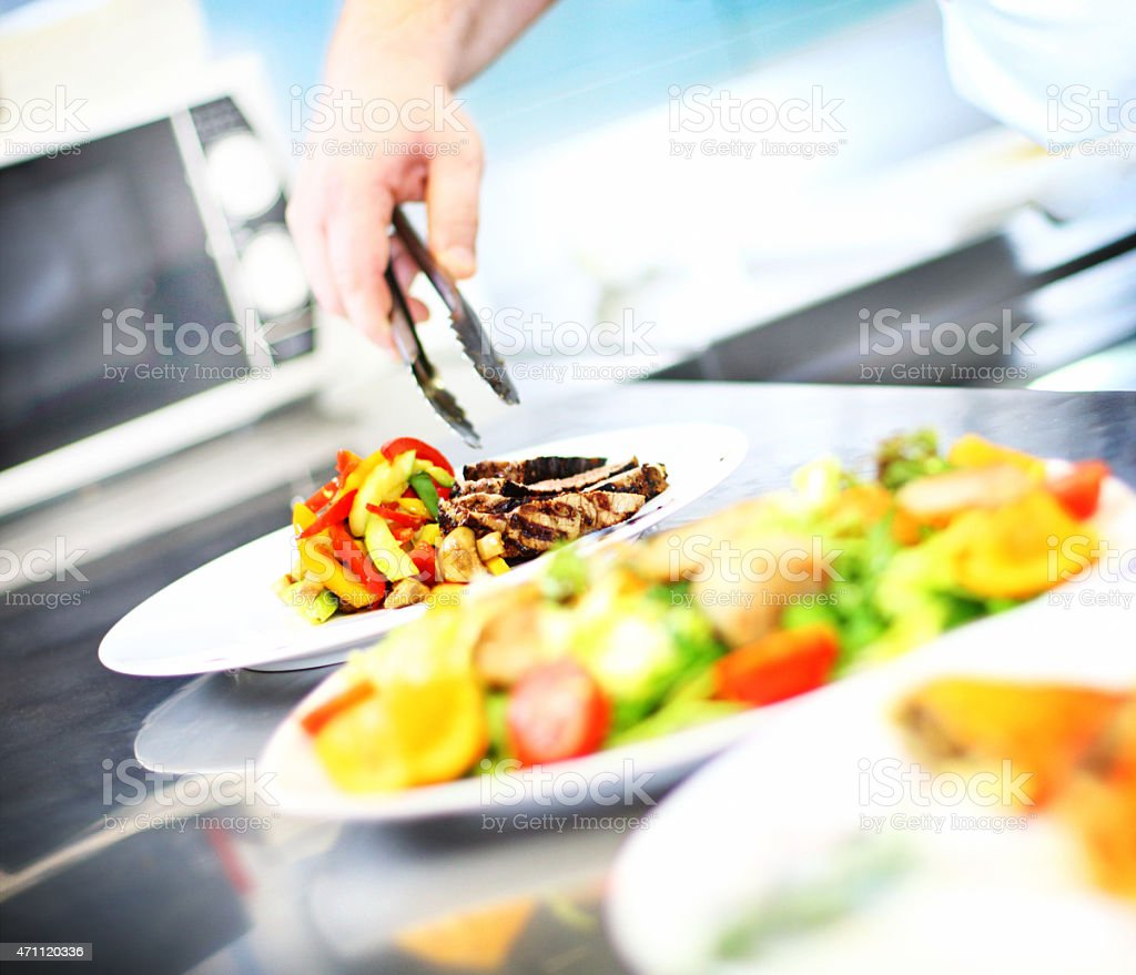 Professional chef placing finishing touches on meal. stock photo