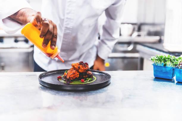 Professional Chef Platting Grilled Chicken Tikka in a Gourmet Kitchen stock photo