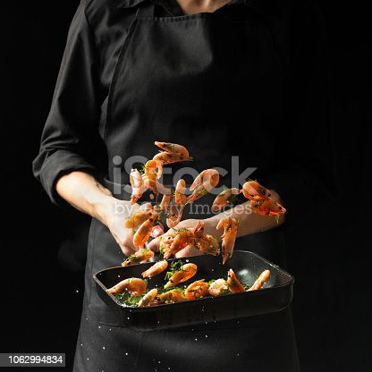 Professional chef prepares shrimps with greens.