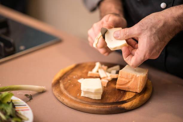 profi-koch zubereitung in privathaus: taleggio käse schneiden - schnittkäse stock-fotos und bilder