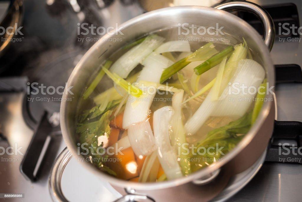 Chef professionnel, préparation de repas dans la maison privée: bouillon de soupe de légumes - Photo