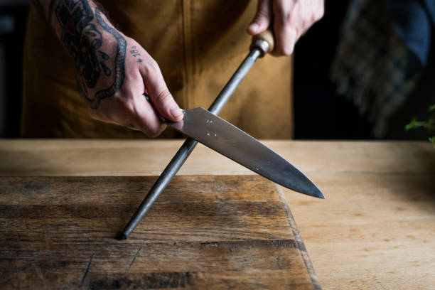 Professional chef sharpening knife in the kitchen stock photo