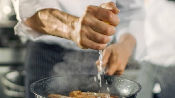 전문 요리사 좋다고 레몬 주스 그것에 빨간 생선 필 레와 뜨거운 팬에. 그는 현대 부엌에서 작동합니다. - 짠 뉴스 사진 이미지
