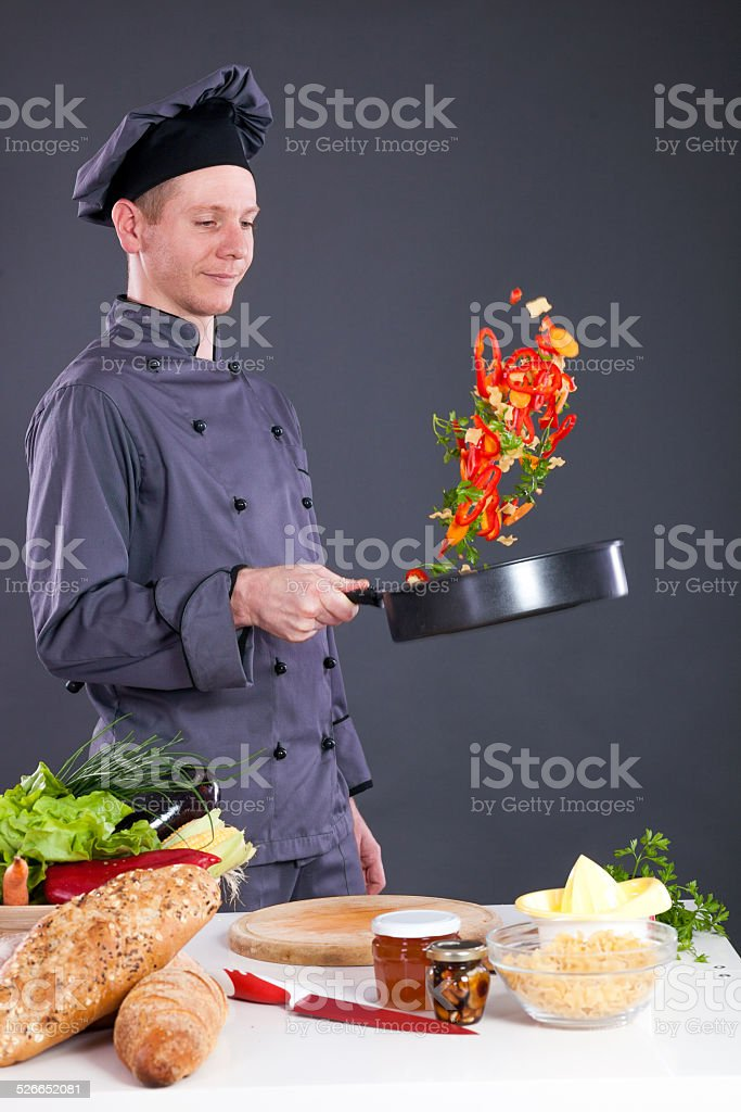professional chef throws food in the pan stock photo