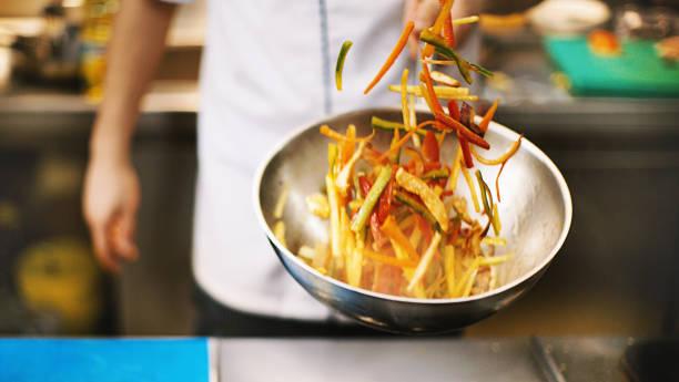 professional chef tossing food. - стир фрай стоковые фото и изображения