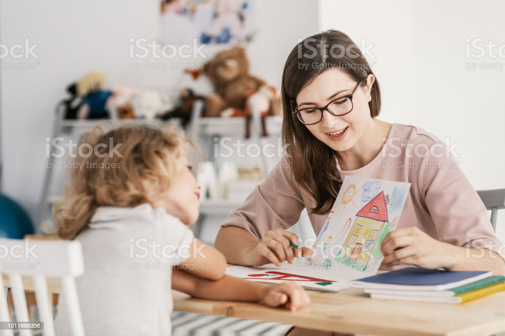 A professional child education therapist having a meeting with a kid in a family support center. stock photo
