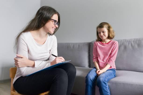 Psicólogo infantil profesional hablando con niña en el cargo - foto de stock