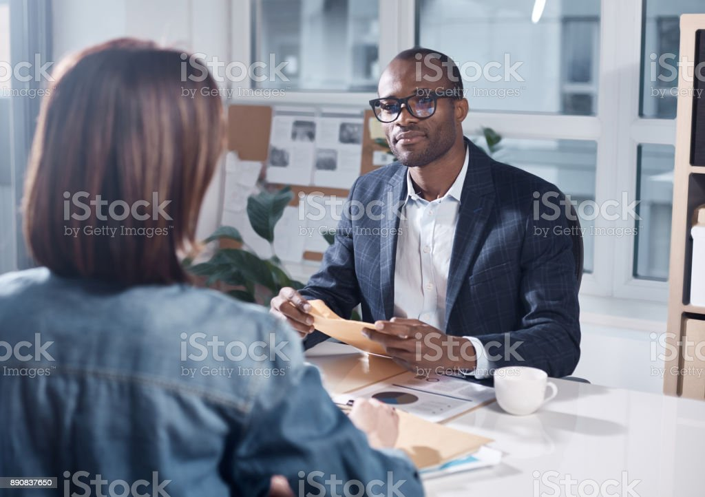 Professional colleagues are discussing project Listen attentively. Skillful young pleasant african businessman in suit is sitting at table and holding papers while looking at responsible colleague female who sitting in front of him Adult Stock Photo