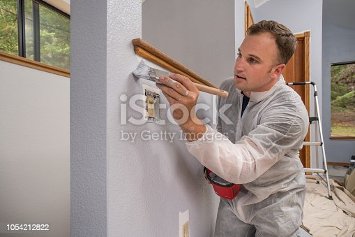 Man painting interior of home in gray paint
