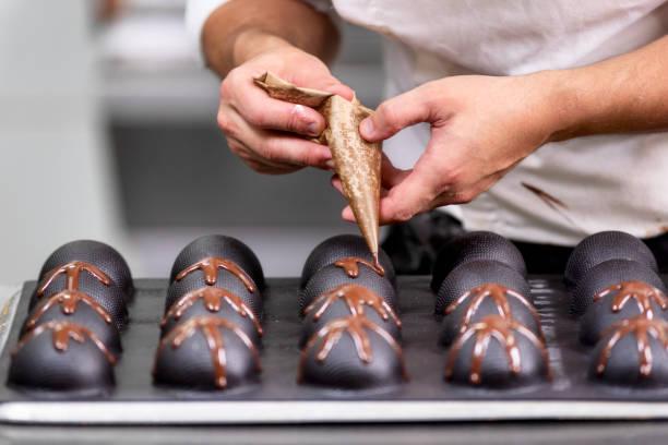 professionele banketbakker die chocolade snoepjes maakt in de snoepwinkel. - hand constructing industry stockfoto's en -beelden