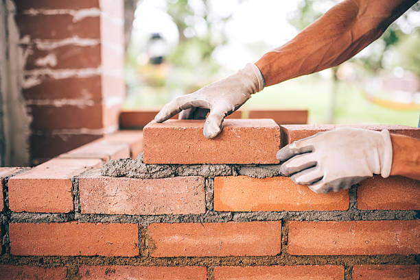professional construction worker laying bricks and building barbecue stock photo